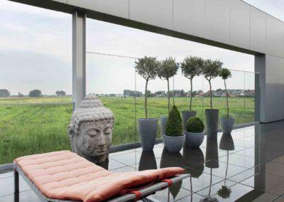 Hoog glazen windscherm en balustrade om uit te kijken over de polders